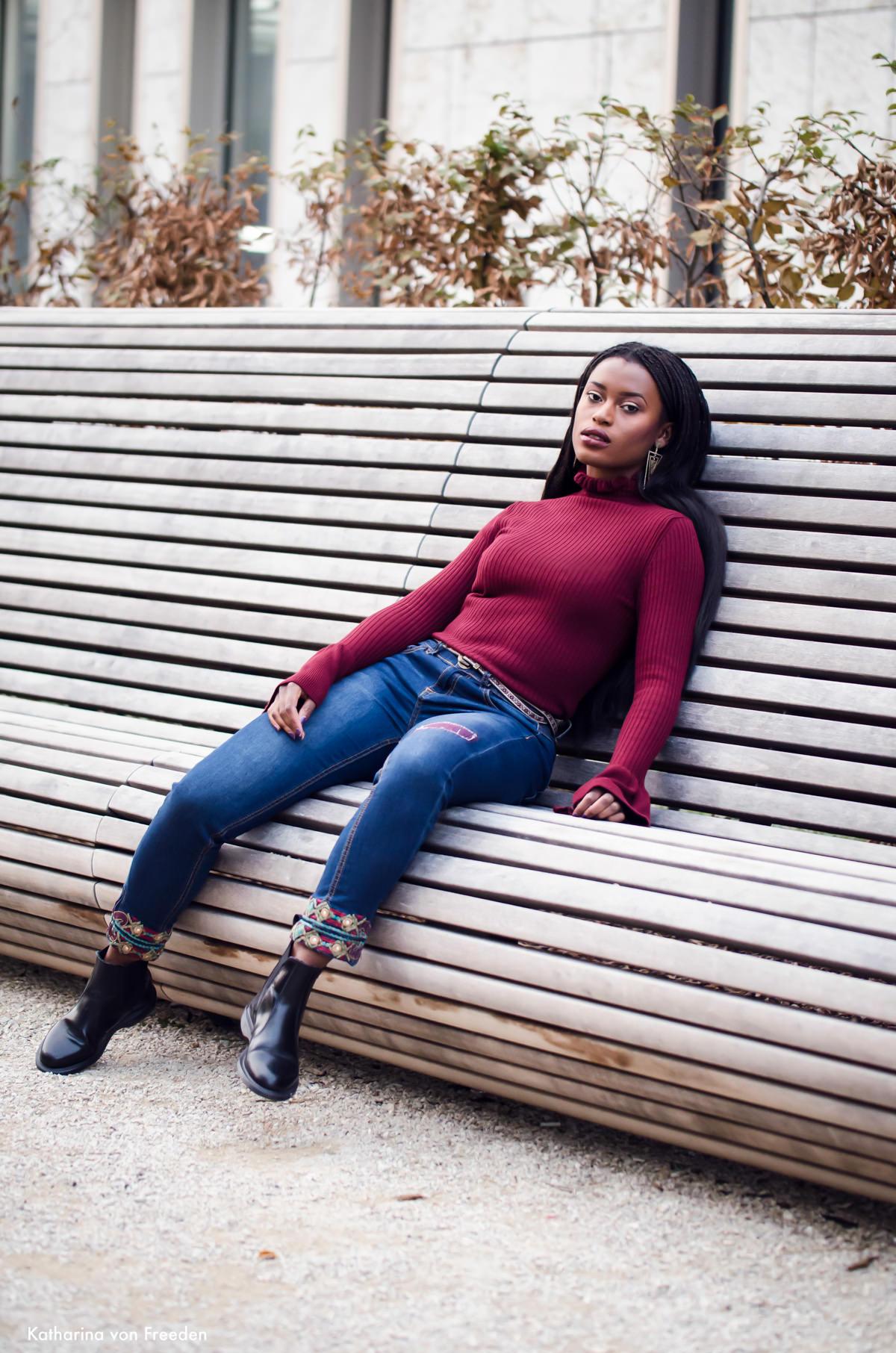 Outfit mit rotem Pullover und Jeans und schwarzen Boots