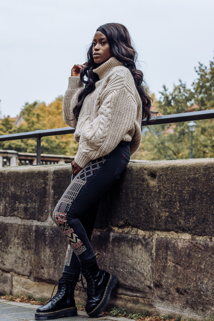 Ama Poku from the blog Phuck it Fashion wearing a chunky knit sweater and embroidered jeans